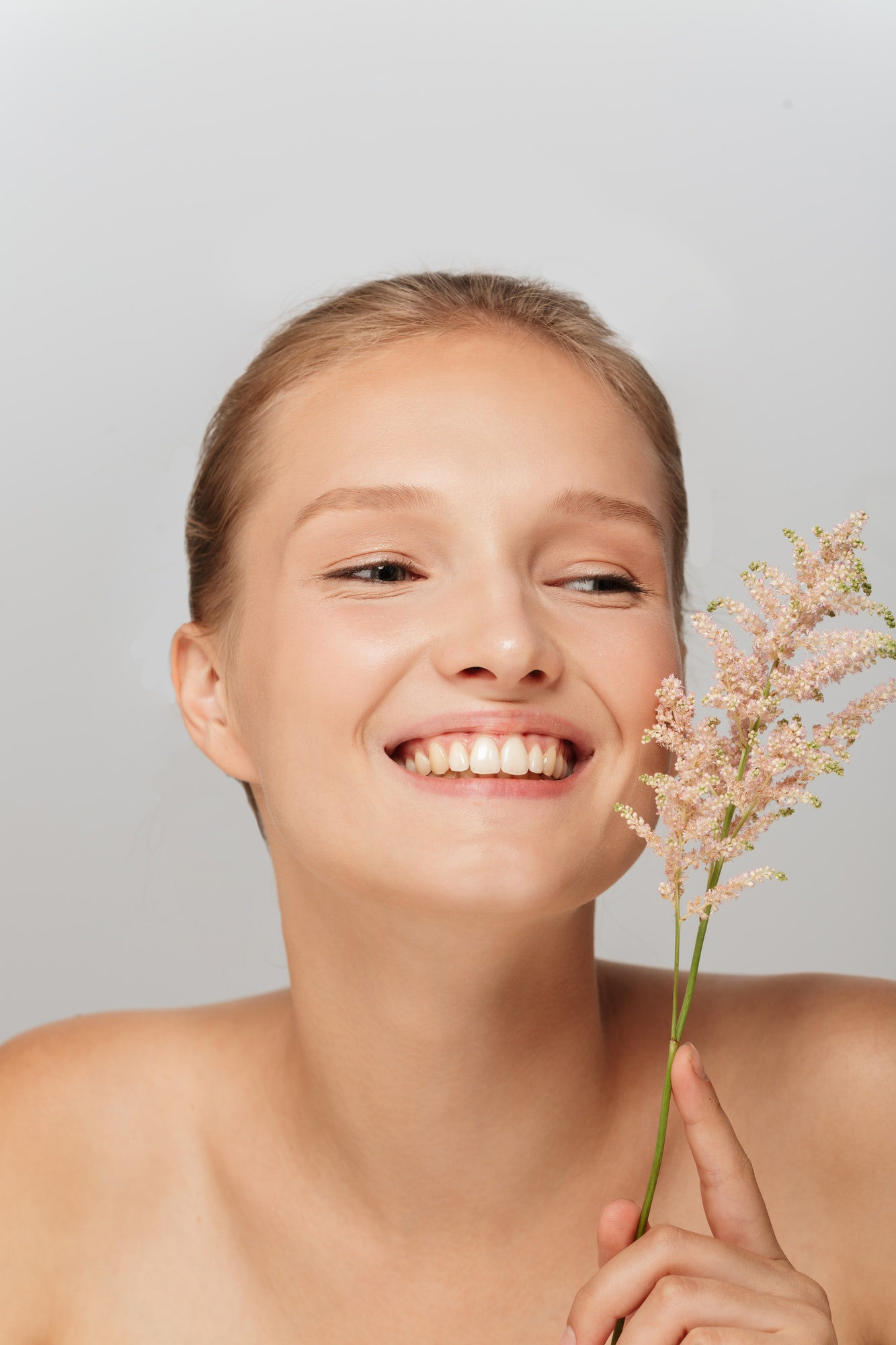 Portrait of young pretty smiling woman without makeup holding be